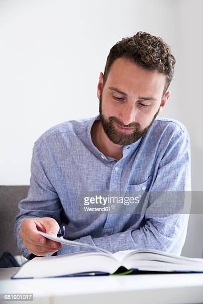Young man reading a book at table