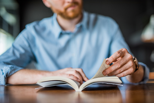Young man reading a book hand close up. 1165926191