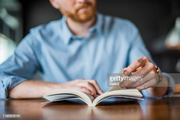 young man reading a book hand close up. - legge foto e immagini stock