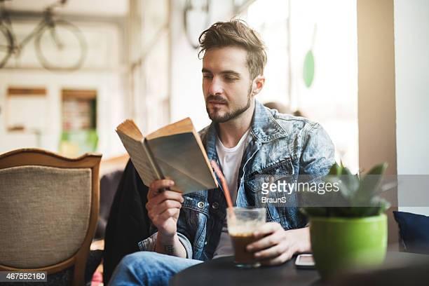 Junger Mann liest ein Buch in einem Café.