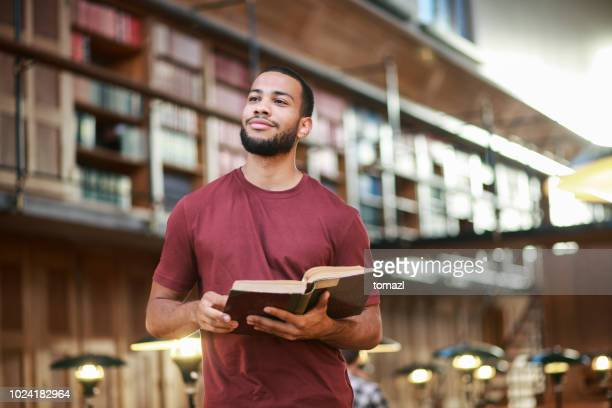 young man reading a book in public library - science photo library stock pictures, royalty-free photos & images