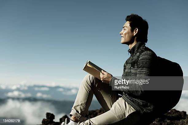 young man reading a book in the mountain