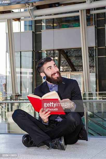 young man (stylish hipster) reading a book outdoor - pjphoto69 stockfoto's en -beelden