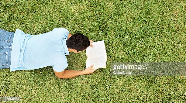 joven leyendo un libro mientras están recostadas en el césped - acostado boca abajo fotografías e imágenes de stock