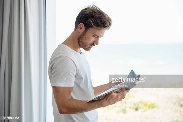 Young man reading a magazine by glass window