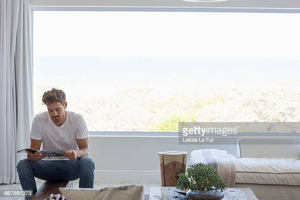 young man reading a magazine in living room at home - erker stockfoto's en -beelden