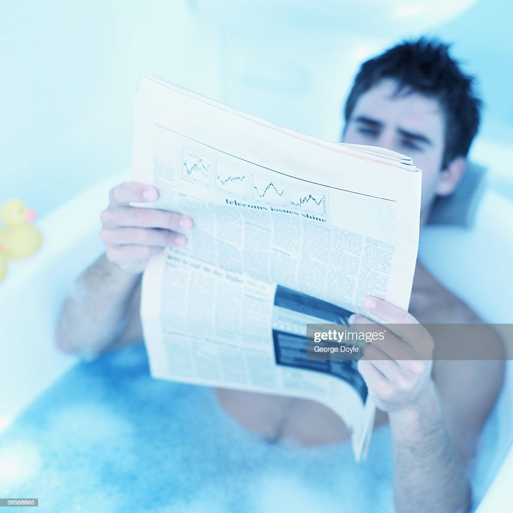 Young Man Reading A Newspaper In A Bathtub Stock Photo | Getty Images