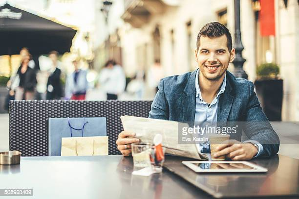 Young man reading a tablet and having breakfast downtown