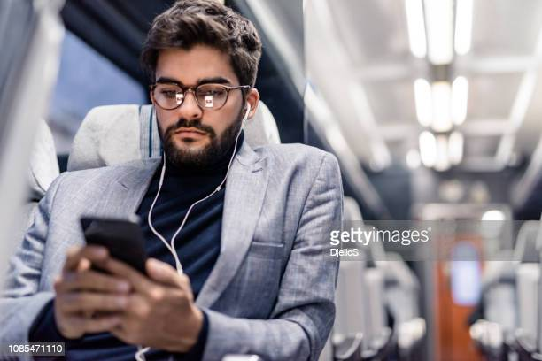 young man reading an article on his phone and listening to podcasts while traveling by train. - listening stock pictures, royalty-free photos & images