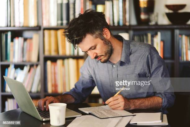 Young man reading and working at home