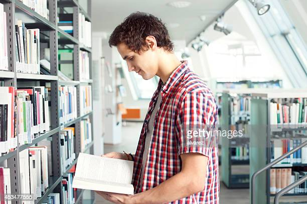 young man reading at the library - one teenage boy only stock pictures, royalty-free photos & images