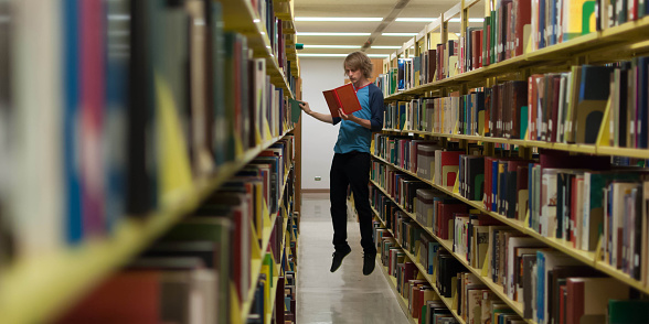 Young man reading book and levitating in library, Fullerton, California, USA - gettyimageskorea