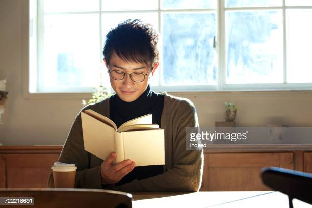 Young man reading book at table