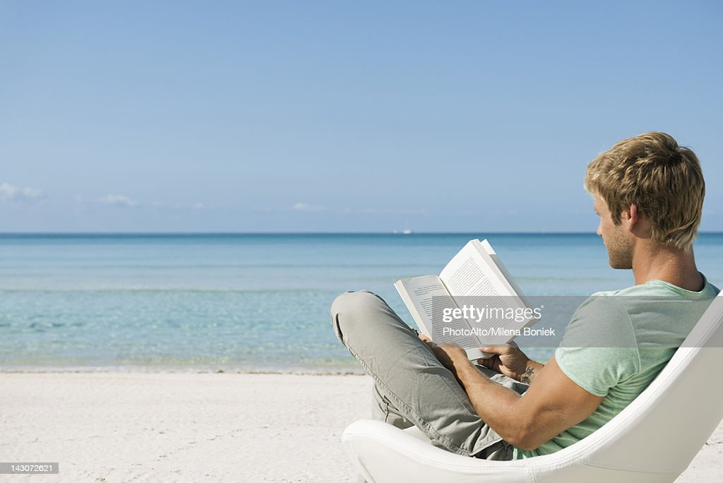 Young man reading book on beach : Stock Photo