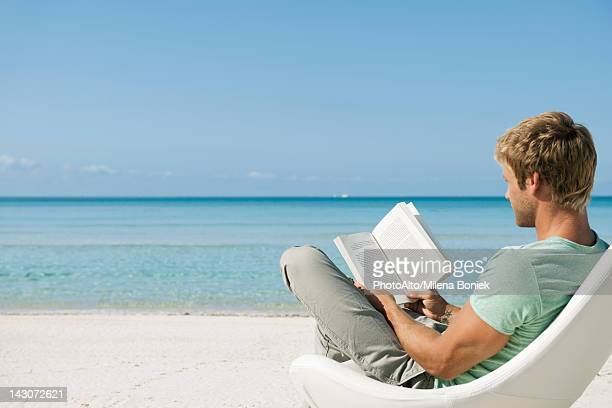 young man reading book on beach - khaki trousers stock pictures, royalty-free photos & images