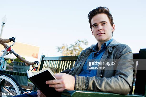 young man reading book on park bench - monrovia california stock pictures, royalty-free photos & images