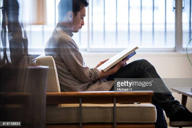 young man reading book on sofa - 趣味 ストックフォトと画像