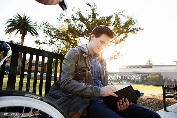 Young man reading book on sunlit park bench