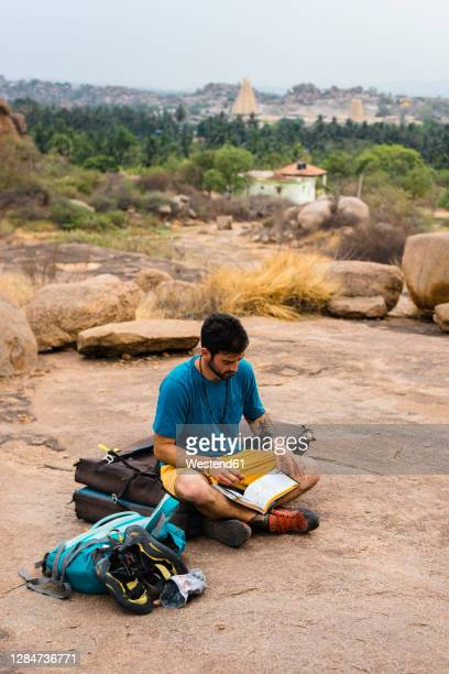 young man reading book while sitting on land, karnataka, hampi, india - karnataka stock pictures, royalty-free photos & images