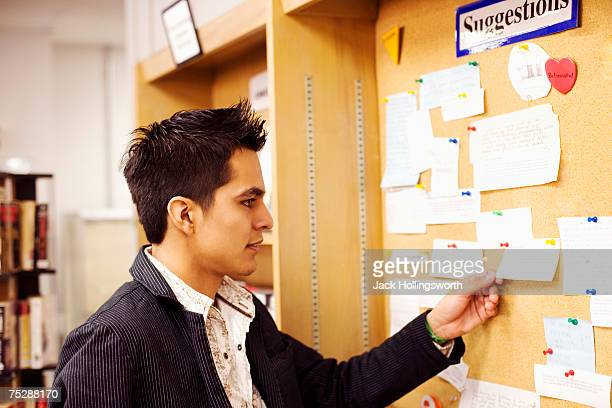 Young man reading cards on bulletin board