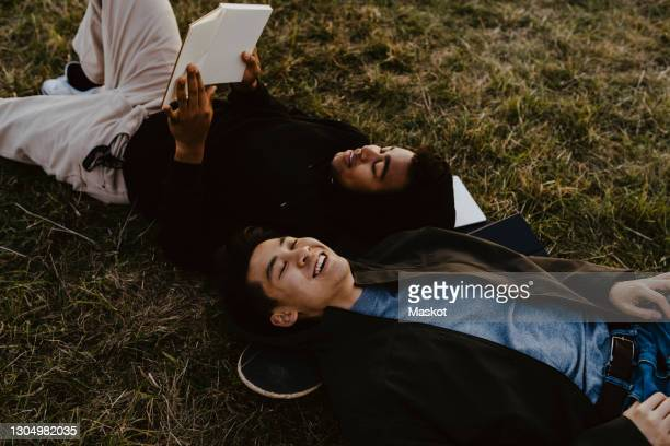 young man reading diary lying down by male friend on grass in park - lying down stock-fotos und bilder