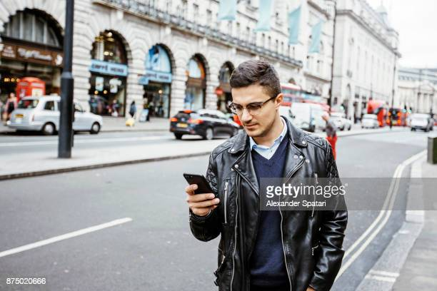 Young man reading from his cell phone on the busy street