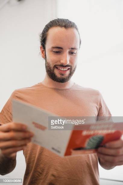 young man reading his birthday card - birthday card stock pictures, royalty-free photos & images