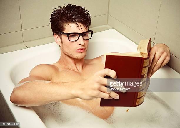 Young man reading in bathtub