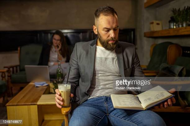 young man reading in cafe - dusan stankovic stock pictures, royalty-free photos & images