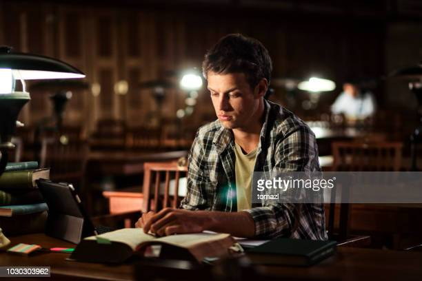 young man reading in library at night - history stock pictures, royalty-free photos & images