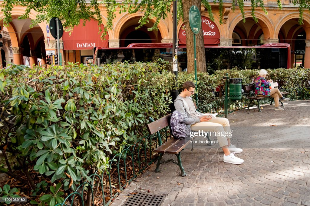 Young man reading in public square of Bologna, Italy. : Stock Photo