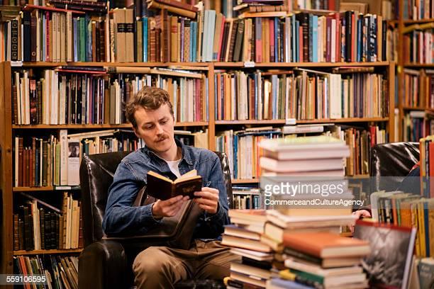 young man reading in second hand bookstore - literatura - fotografias e filmes do acervo