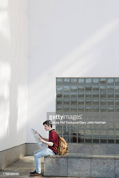 Young man reading map by glass bricks