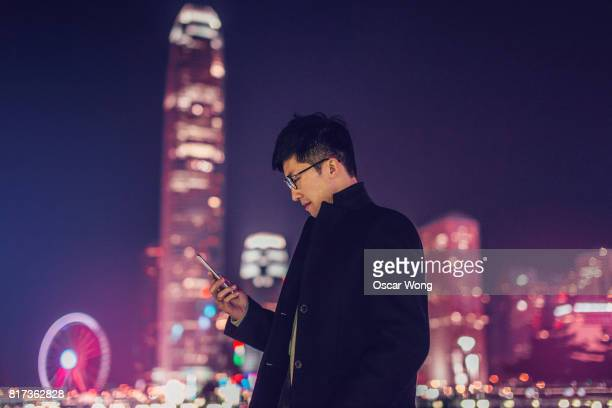 Young man reading message on phone against cityscape at night