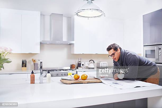 Young man reading newspaper at kitchen counter