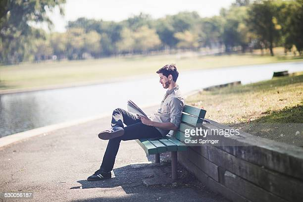 Young man reading newspaper on bench in park