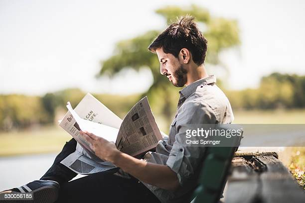 Young man reading newspaper on park bench