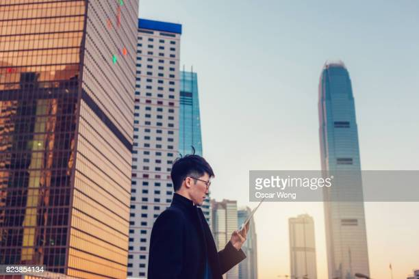 Young man reading on his tablet with Hong Kong cityscape background