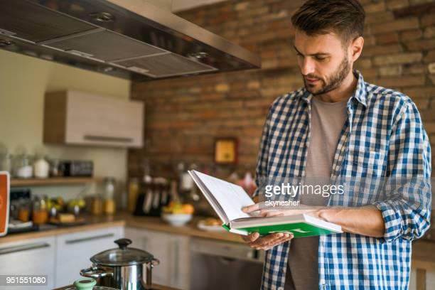 junger mann lesen rezept aus einem kochbuch in der küche. - kochbuch stock-fotos und bilder