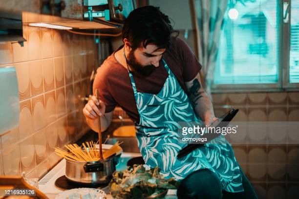 young man reading recipe on digital tablet and cooking - tutorial stock pictures, royalty-free photos & images