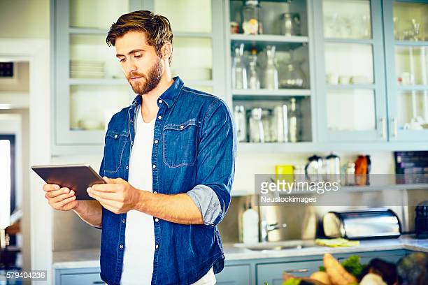 Young man reading recipe on digital tablet in kitchen