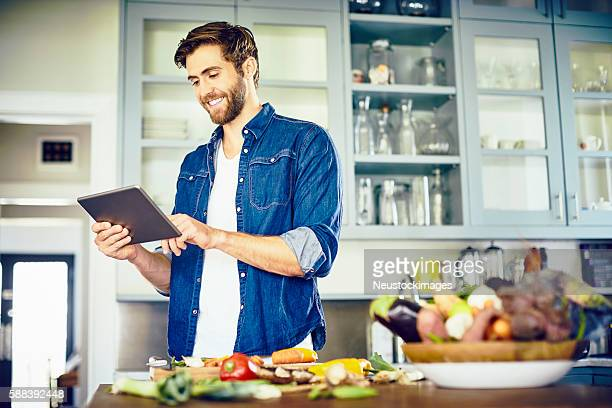young man reading recipe on tablet computer in kitchen - convenience stock photos and pictures