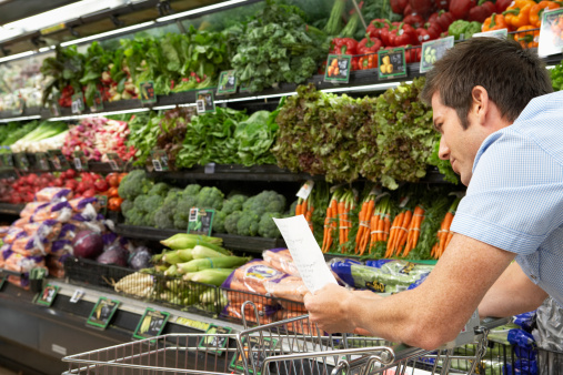 Young man reading shopping list in produce aisle, side view, close-up - gettyimageskorea