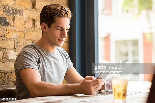 Young man reading smartphone text in bar