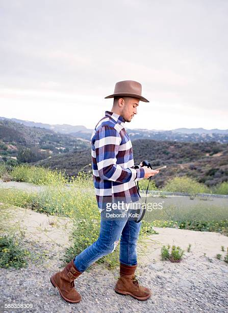 Young man reading smartphone text on rural hill