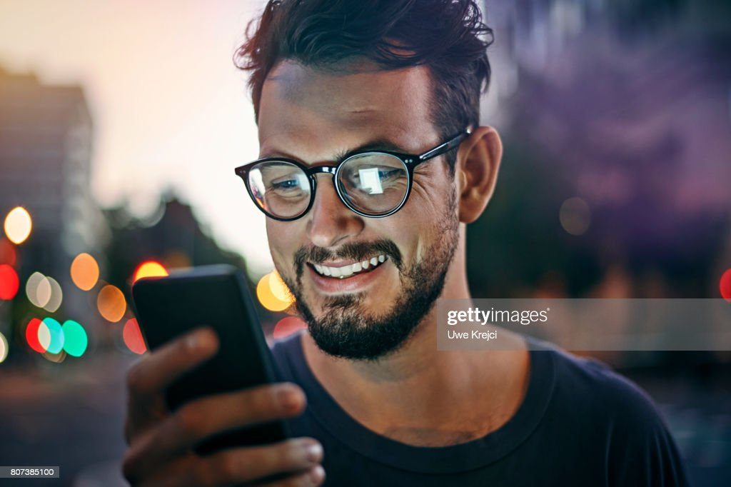 Young man reading text message : Stock Photo
