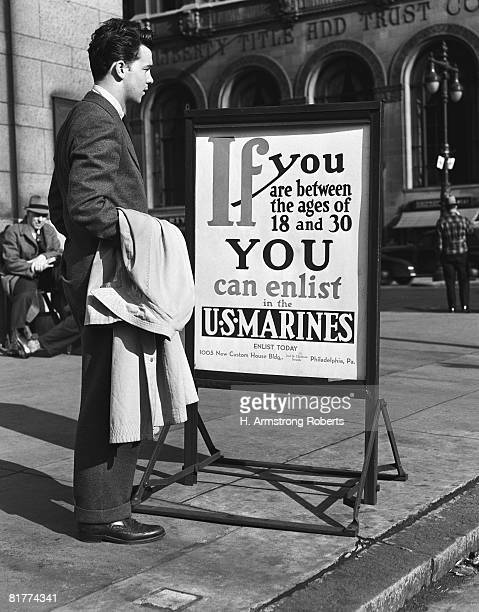 Young man reading US Marines recruitment post. (Photo by H. Armstrong Roberts/Retrofile/Getty Images)