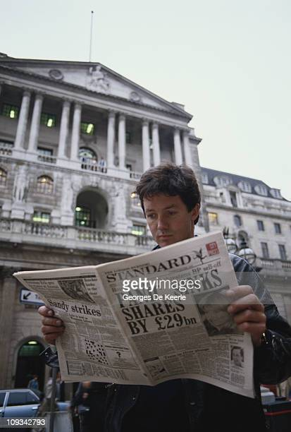 Young man reads a copy of the Evening Standard in London, with a headline referring to that day's stock market crash, known as Black Monday, 19th...