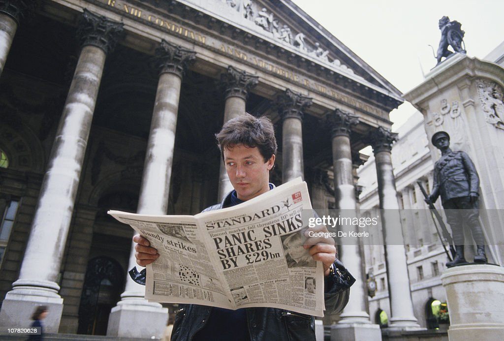A young man reads a copy of the Evening Standard outside the Royal Exchange in London, with a headline referring to that day's stock market crash, known as Black Monday, 19th October 1987.