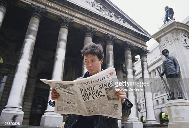 A young man reads a copy of the Evening Standard outside the Royal Exchange in London with a headline referring to that day's stock market crash...